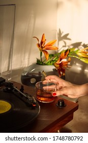Woman's Hand Holding THC CBD Joint and Whiskey Glass at a record player.