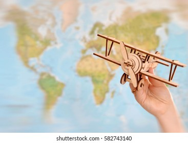 woman's hand holding toy airplane against map of world. empty space you can place your text or information. blur picture
