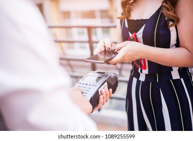 A woman's hand holding and using of smart phone to pay for goods to a cashier. Shopping concept.