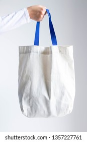 A woman's hand holding white cotton shopping eco bag with blue handle in soft focus; concept of recycle and save the earth.