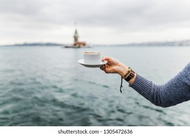 A woman's hand is holding a white cup of hot milky beverage with cinnamon called Turkish salep (sahlep) on the background of rippling water and misty Maiden's Tower in the distance, Istanbul.
