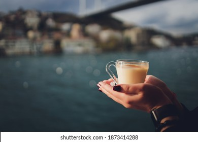 A woman's hand is holding a white cup of hot milky beverage with cinnamon called Turkish salep sahlep on the background of rippling water and misty Maiden s Tower in the distance, Istanbul.