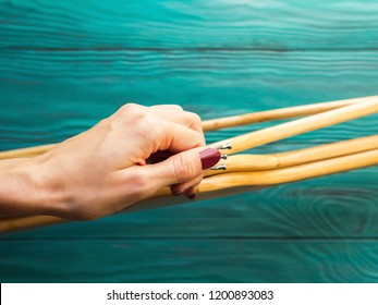 Woman's hand holding wooden hangers on green background. What, nothing to wear. Wardrobe building concept. Shopping, sale. Minimalism, purging