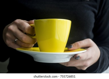 Woman's hand holding a yellow cup of coffee