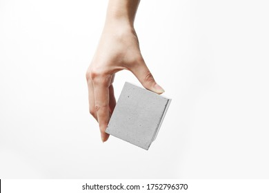 A woman's hand holds a box made of concrete
