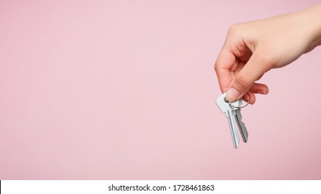 a woman's hand holds a bunch of two keys on a pink background. for copy space