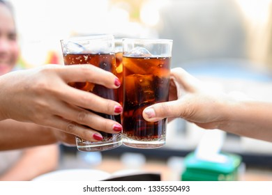 The woman's hand holds a glass of black soft drinks to drink.