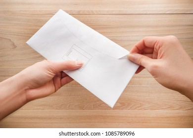 Woman's hand holds and opens a white paper envelope or letter envelopes on a wooden desk top view background.