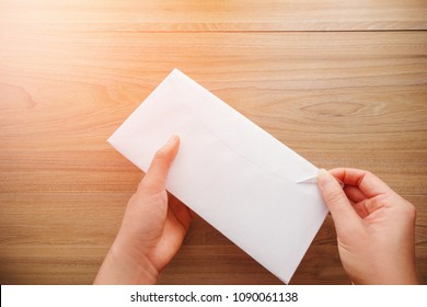 Woman's hand holds and opens a white paper envelope or letter envelopes on a wooden desk with natural sunlight in morning, Top view background.
