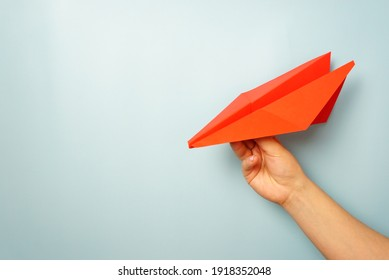 A woman's hand holds a red paper airplane on a pale blue background. copy space