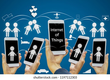 woman's hand holds a smartphone with an icon on a mobile screen on  blue background isolated; With concept of internet of things (IOT), connection of intelligent devices over Internet with convenience