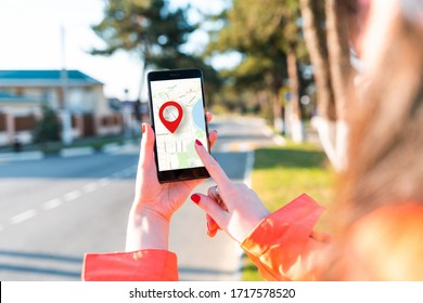 A woman's hand holds a smartphone with an online map that has a red geolocation icon on it. In the background, there is a blurred street.Close up. Concept of online navigation and GPS