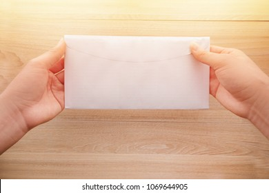 Woman's hand holds a white long paper envelope or letter envelopes on a wooden desk with natural sunlight in morning, Top view background.