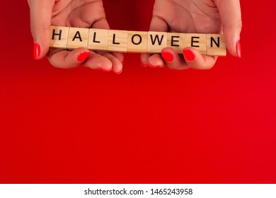 A woman's hand holds a wooden square with an inscription halloween on a red background