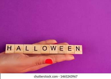 A woman's hand holds a wooden square with an inscription halloween on a purple background