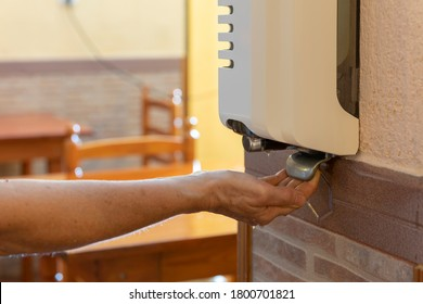 Woman's hand with hydroalcoholic gel dispenser in a coffee shop
