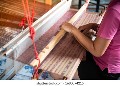 The woman's hand is intentionally weaving silk.