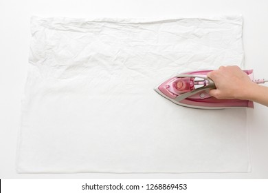 Woman's hand ironing clean, crumpled white cloth on board. Before and after. Daily routine. Pink, modern electric iron with steam system. Closeup. Top down view.