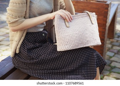 Woman's hand with knitted handbag. Stylish woman in gray shirt and knitted beige jacket sitting in the park with beige handbag. Street look, casual fashion concept