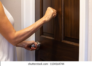 woman's hand knocking on a brown wooden door and turning a doorknob, medium shot, side view, horizontal photo