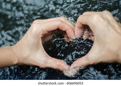 Woman's hand making heart shape in the water