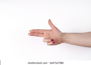 Woman's hand making shooting gun, gesture. hand pistol gesture on isolated white background. Woman hand pointing with two fingers.