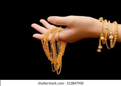 woman's hand with many different gold jewelry on black background