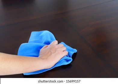 woman's hand with microfiber cloth polishing dark wood