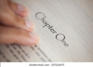 """Woman's hand on book page with title """"Chapter One"""". Shallow depth of field."""