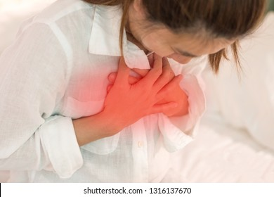 Woman's hand on chest with red spot as suffering on chest pain. Female suffer from heart attack,Lung Problems,Myocarditis, heart burn,Pneumonia or lung abscess, pulmonary embolism day
