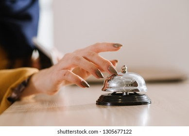 A womans hand on the hotel bell at the reception
