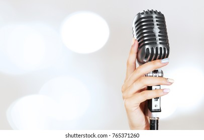 Woman's hand on retro microphone