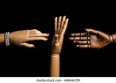 A woman's hand and one hand of black man meet. A white hand opposes. Isolated on black background. With copy text space