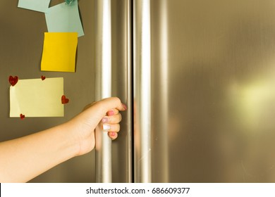Woman's hand open refrigerator with note on the door