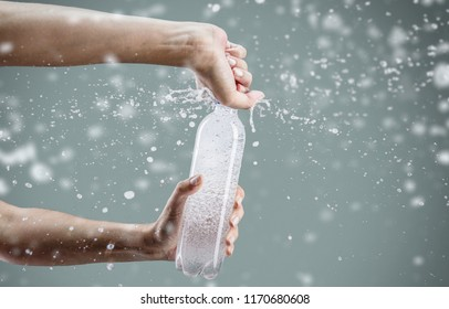 Woman's hand opening a bottle with sparkling water with splashes and lot of drops on gray background. Studio photo shooting. Concept of health lifestyle