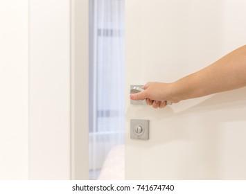 Woman's hand opening door in bedroom