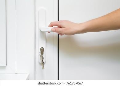 Woman's hand opening the white  plastic door.
