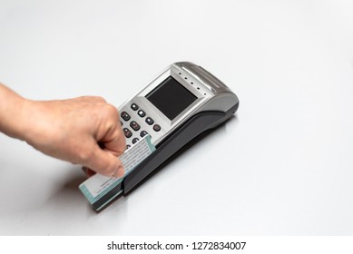 Woman's hand passing credit card by a dataphone, card reader to charge in time of sales.