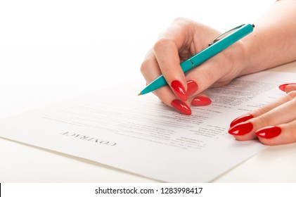 woman's hand with pen signing document