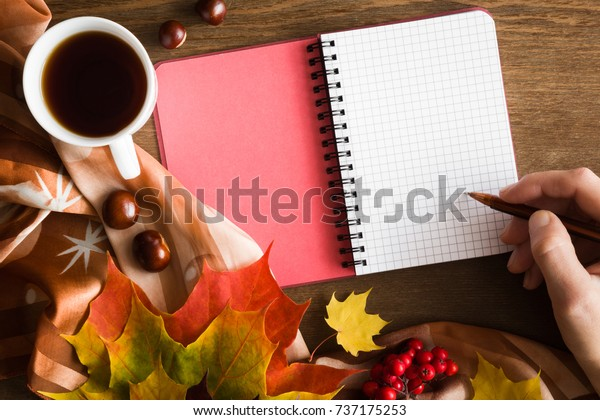 Woman's hand with pen writing in the notebook. Cup of maple tea with colorful maple leaves on the brown wooden table. Writing concept with autumnal mood. Empty place for a text. Top view.