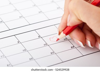 Woman's hand with pencil try to drawing heart shape in calendar in Valentines day