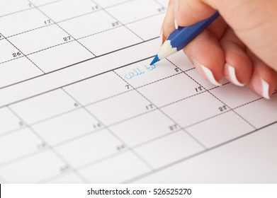 Woman's hand with pencil try to write reminder in calendar