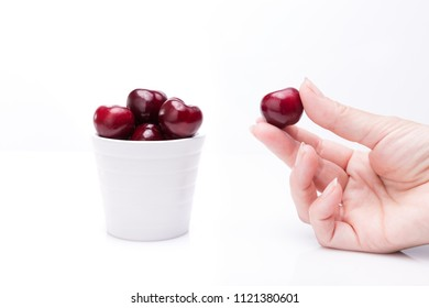 Woman's hand picking california cherry on white background