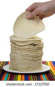 A woman's hand picks up a corn tortilla from a big stack of tortillas.