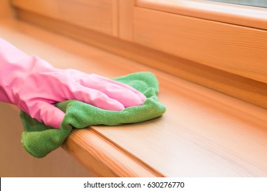 Woman's hand in pink rubber protective glove with dry rag wiping wooden window sill  from dust. Early spring cleaning or regular clean up. Maid cleans house.