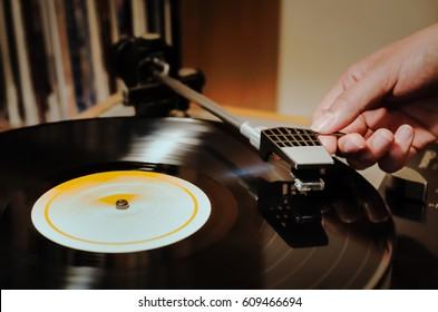 Woman's hand placing the needle on a record