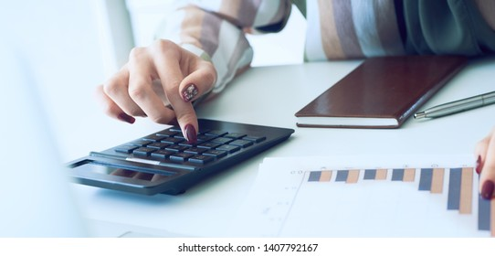 A woman's hand pointing on summary report chart and calculate finance in office close-up.