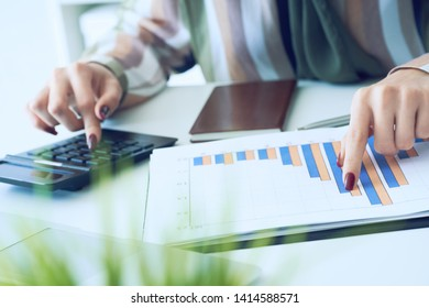 A woman's hand pointing on summary report chart and calculate finance in office.
