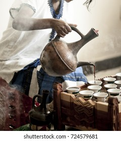 Womans hand pouring coffee for traditional Ethiopian coffee ceremony