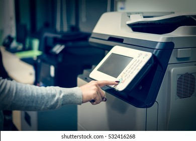 Woman's hand press button on panel of printer at office.